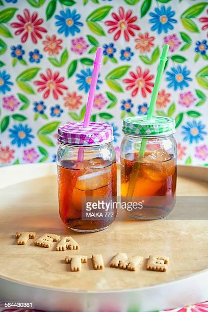 Two mason jars of iced tea with straws