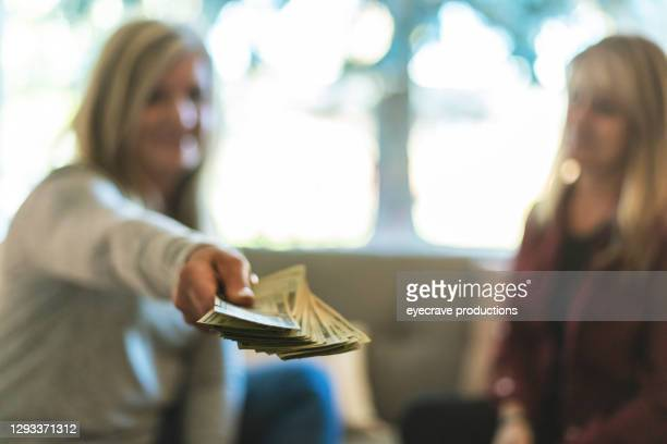 two mature adult women counting and handling money - eyecrave  stock pictures, royalty-free photos & images
