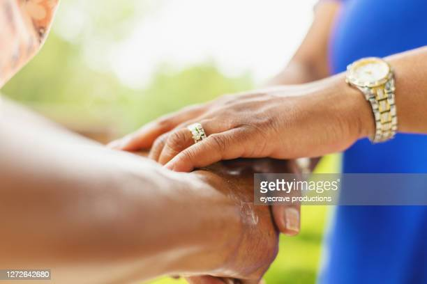 two mature adult women holding hands - eyecrave  stock pictures, royalty-free photos & images