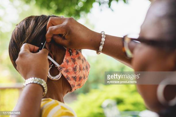 two mature adult women putting on face masks daughter assisting elderly mother - eyecrave  stock pictures, royalty-free photos & images