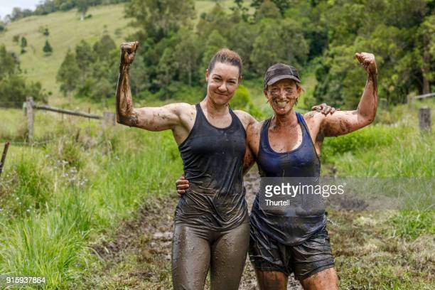 two mature age women celebrating after completing mud run fitness session - obstacle course stock pictures, royalty-free photos & images
