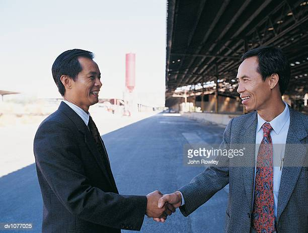Two Mature Businessman Shaking Hands Outside a Factory Building