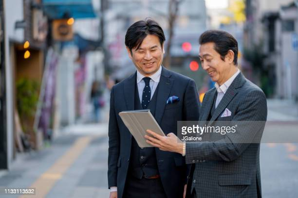 Two mature businessmen meeting outdoors and looking at a digital tablet