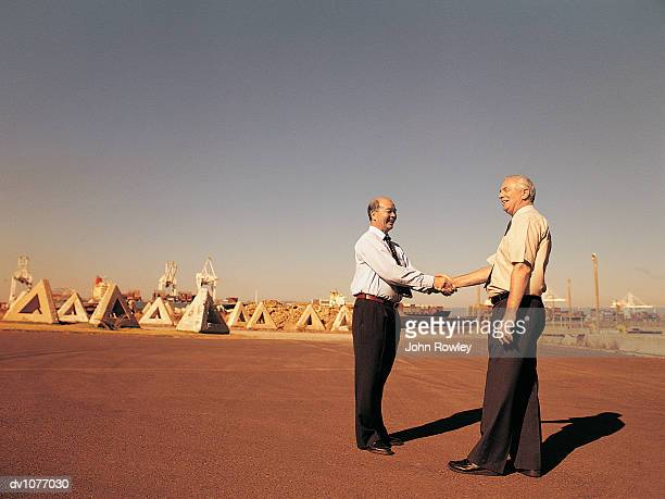 Two Mature Businessmen Shaking Hands in an Industrial Park