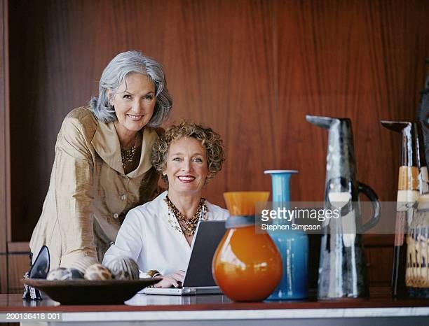two mature businesswomen, one sitting at desk with laptop, portrait - kunsthändler stock-fotos und bilder