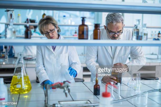 Two mature chemists analyzing liquid in a beaker while working in a laboratory.
