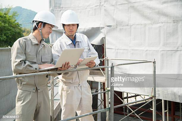 Two mature construction workers talking and looking at plans