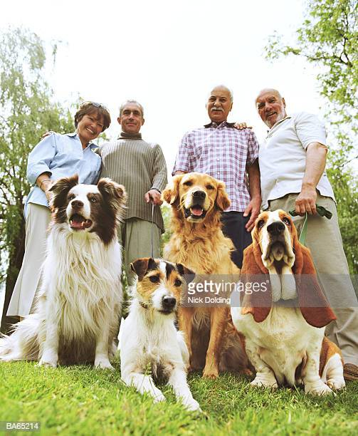 Two mature couples and four dogs in park,  portrait