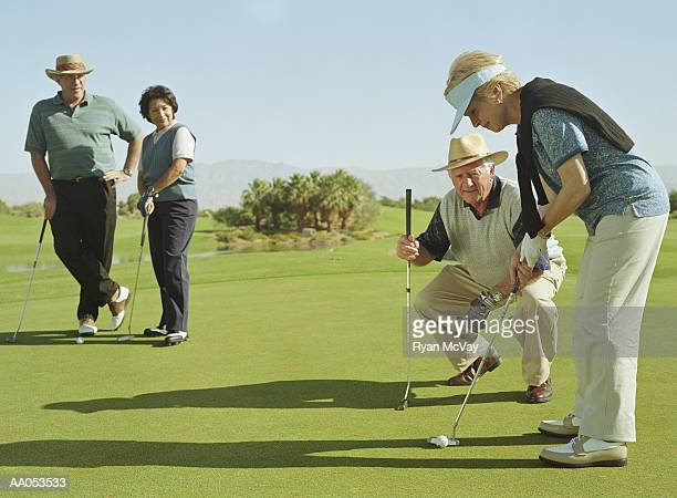 two mature couples golfing, woman lining up shot - golf sport stockfoto's en -beelden