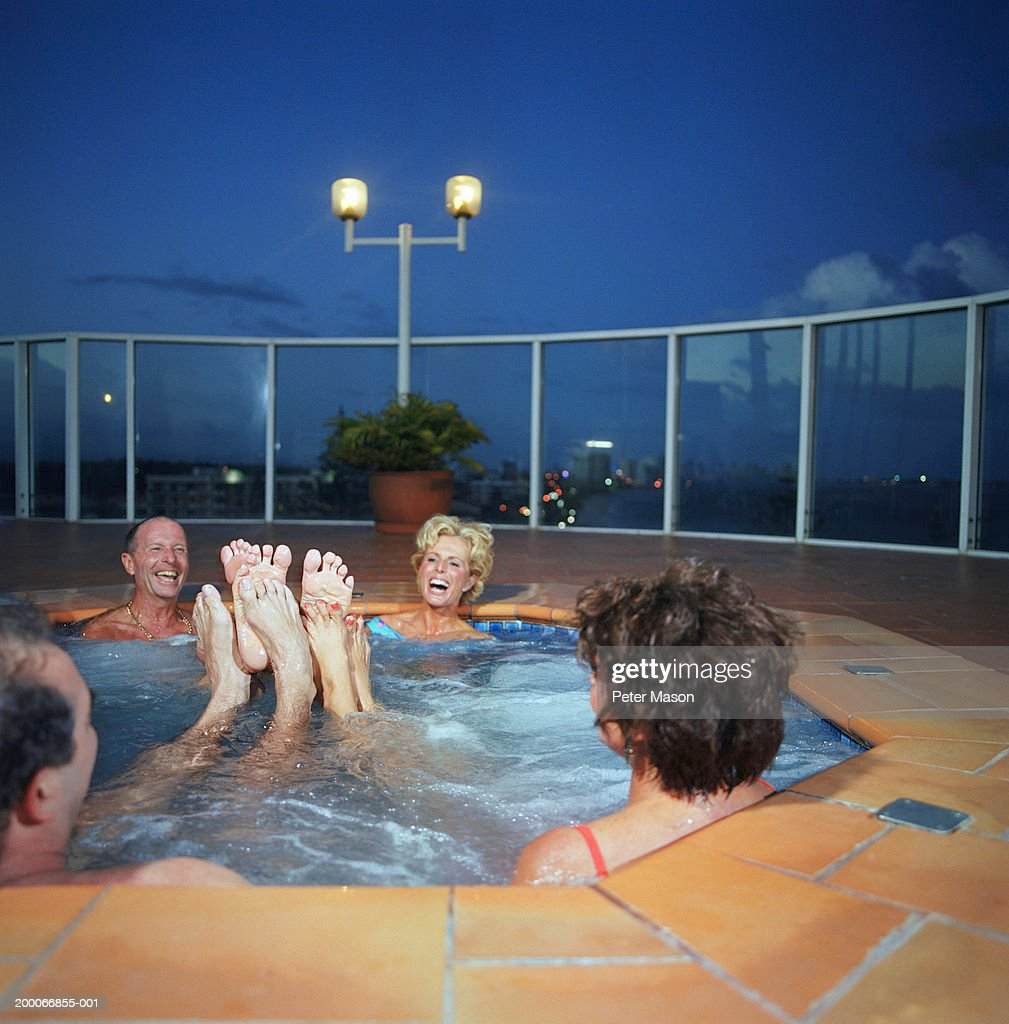 Two mature couples playing footsie in hot tub : Stock Photo