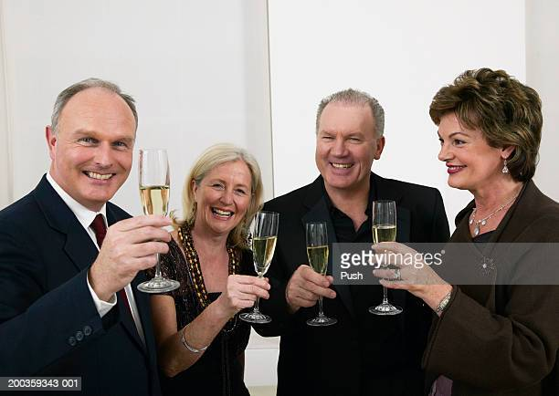 Two mature couples raising glasses of white wine, smiling