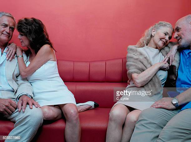Two Mature Couples Sitting on Red Couch