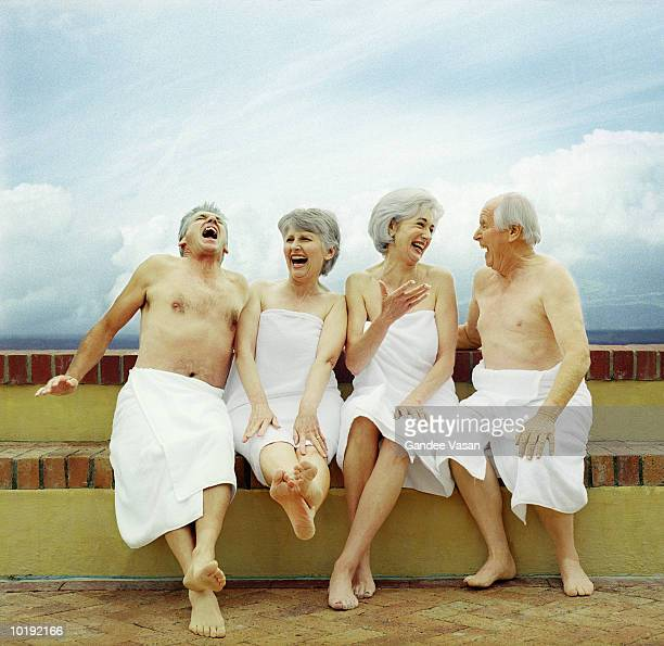 Two mature couples sitting on wall wearing towels, laughing