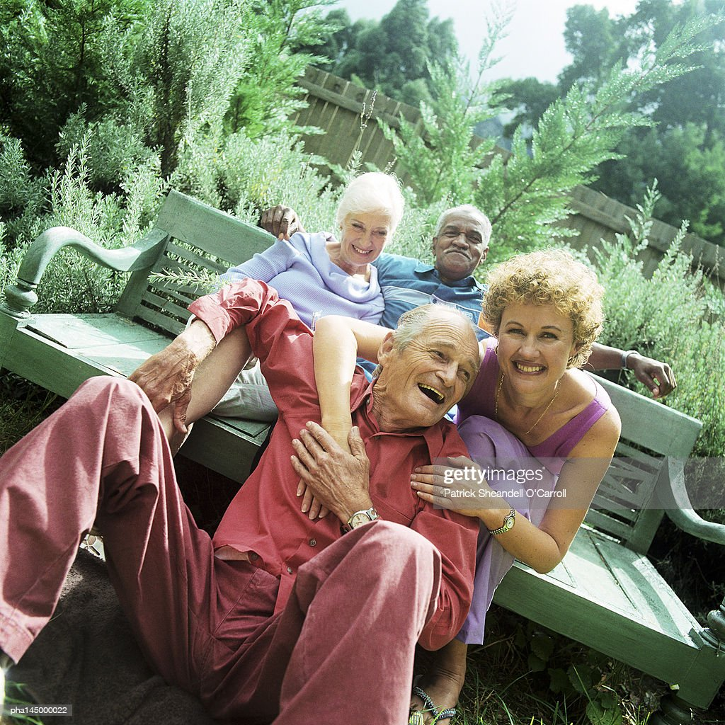 Two mature couples sitting outdoors, smiling : Stockfoto