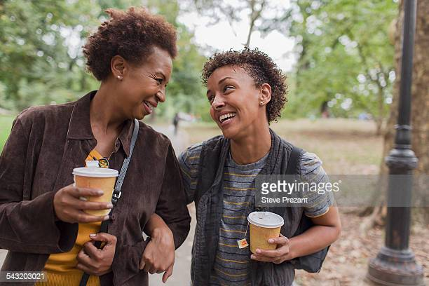 Two mature female friends drinking takeaway coffee whilst strolling in park