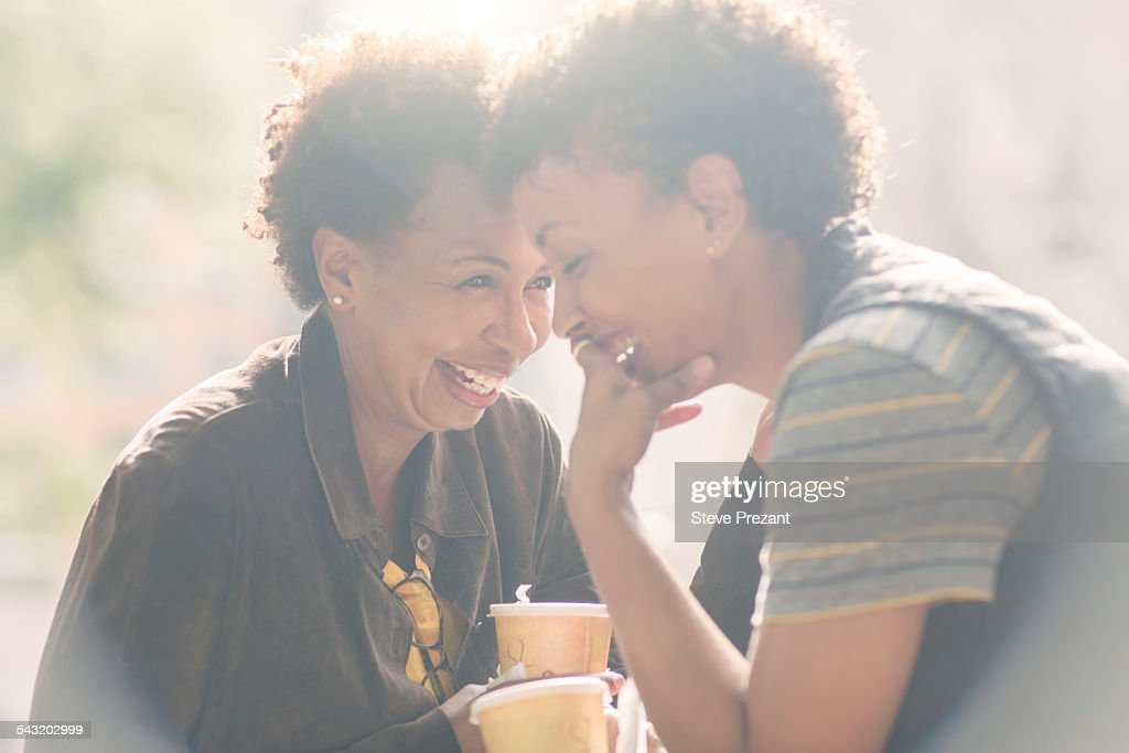 Two mature female friends laughing whilst drinking takeaway coffee on street : Stock Photo