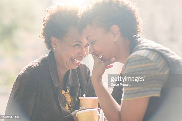 two mature female friends laughing whilst drinking takeaway coffee on street - overexposed stock pictures, royalty-free photos & images