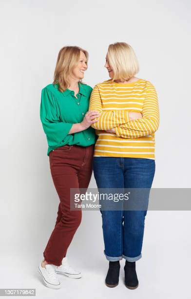 two mature female friends standing together - female friendship stock pictures, royalty-free photos & images