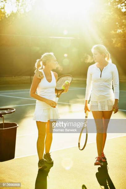 Two mature female tennis players in discussion after early morning match