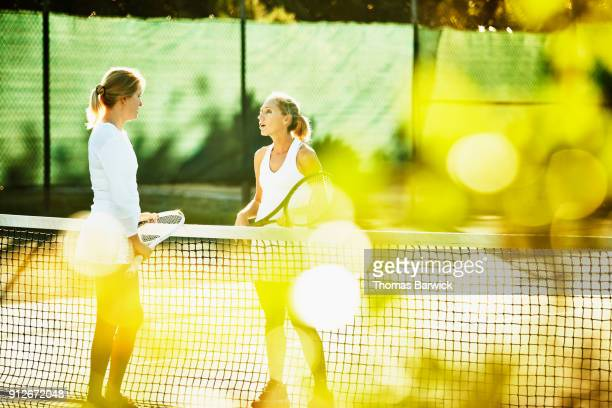 Two mature female tennis players in discussion at net after early morning tennis match