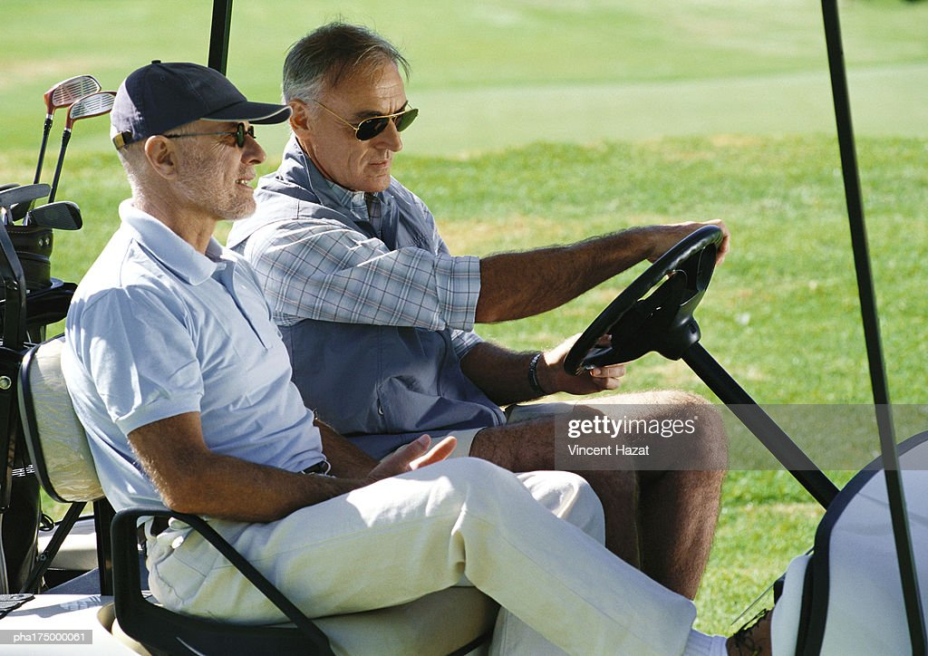 Two mature golfers in golf cart, close-up, side view : Stockfoto