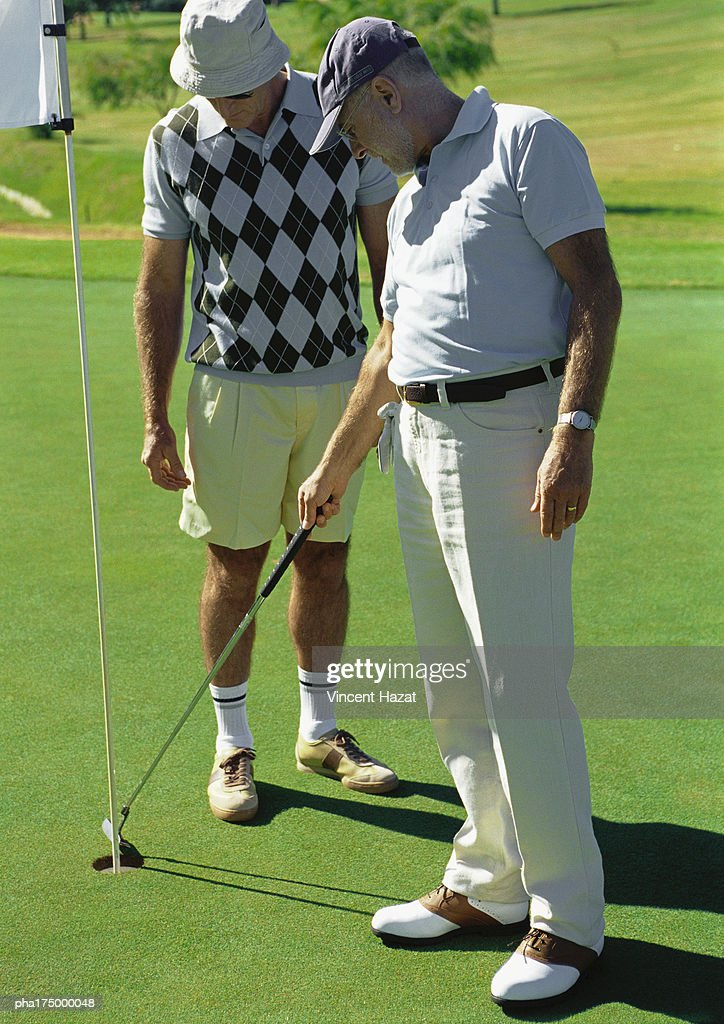 Two mature golfers looking at hole : Stockfoto