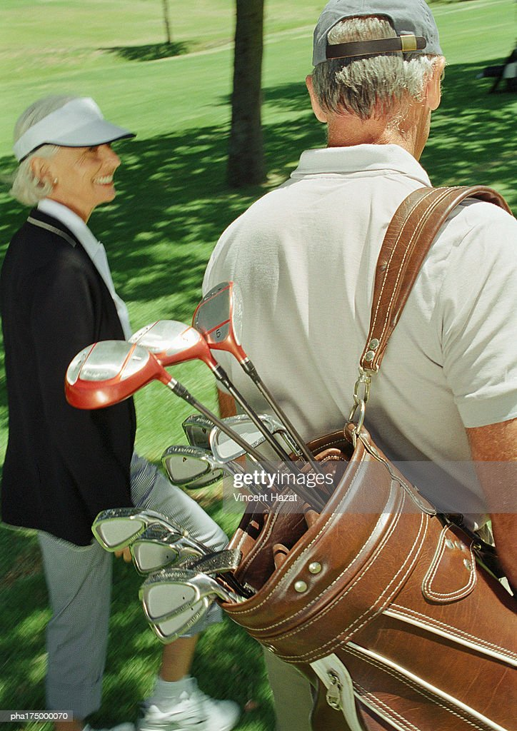 Two mature golfers, one carrying clubs, rear view : Stockfoto
