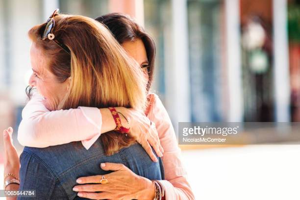 two mature hispanic female friends in full embrace as they reunite - congratulations stock pictures, royalty-free photos & images