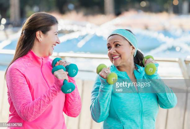 two mature hispanic women exercising with handweights - hand weight stock pictures, royalty-free photos & images