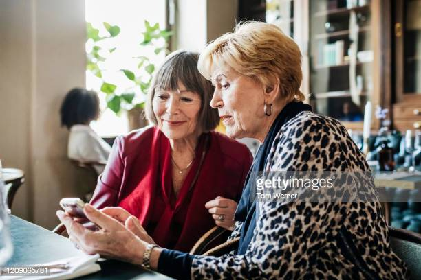 two mature ladies looking at smartphone in restaurant - bonding stock pictures, royalty-free photos & images