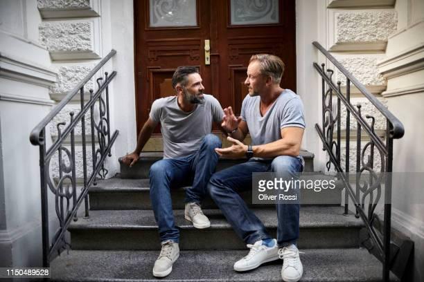 two mature male friends sitting on front stoop talking - nur männer stock-fotos und bilder
