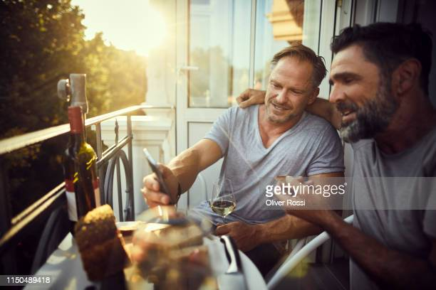 two mature male friends with cell phone having dinner on balcony - avondschemering stockfoto's en -beelden