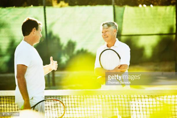 Two mature male tennis players in discussion at net after tennis match