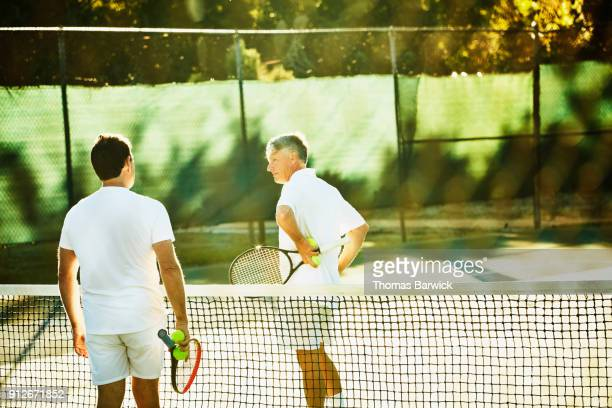 Two mature male tennis players in discussion at net during early morning tennis match
