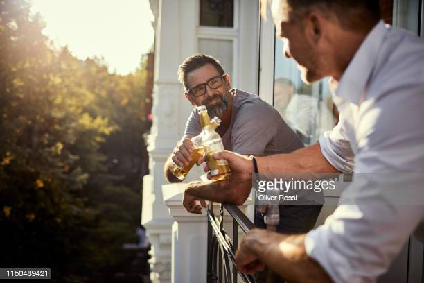 two mature men having a beer on balcony - balcony stock pictures, royalty-free photos & images