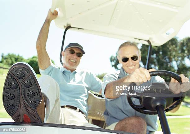 Two mature men in golf cart, smiling, close-up