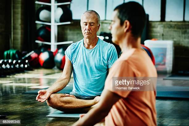 Two mature men in lotus pose during class
