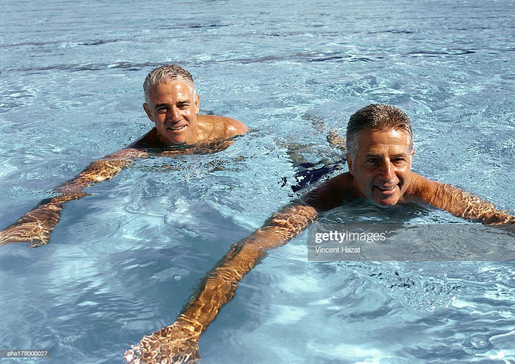 Two mature men in swimming pool, smiling : Stockfoto