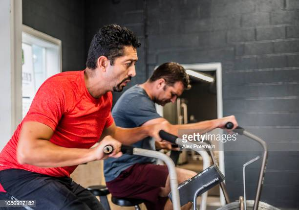 two mature men, latino and caucasian, doing cycling exercise in the gym - alex potemkin or krakozawr latino fitness stock photos and pictures