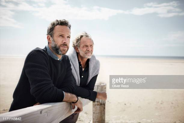 two mature men leaning on railing of boardwalk on the beach - mature adult stock pictures, royalty-free photos & images
