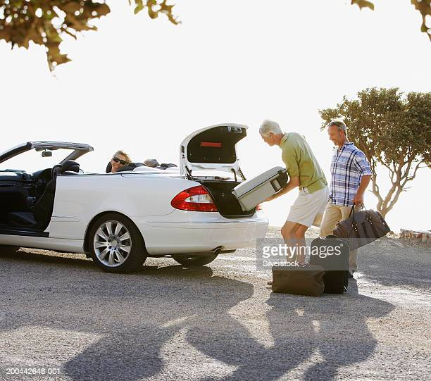Two mature men loading luggage into car, two women sitting in back