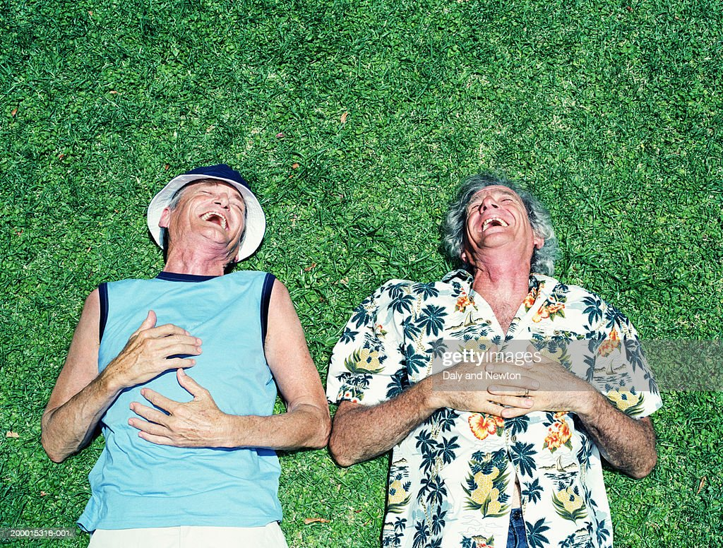 Two mature men lying on grass, laughing, overhead view : Foto de stock