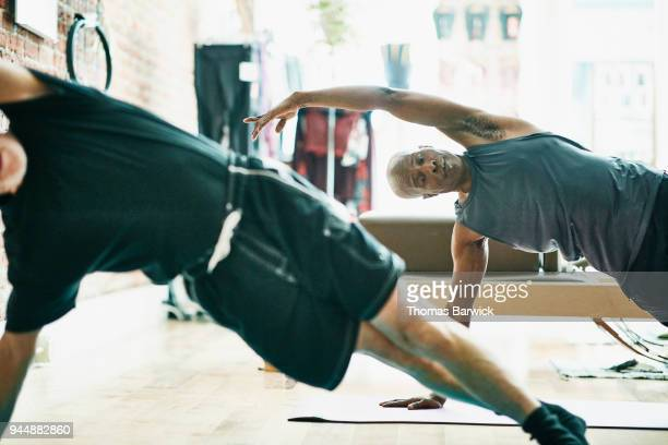 Two mature men performing side plank on mat during pilates class in exercise studio