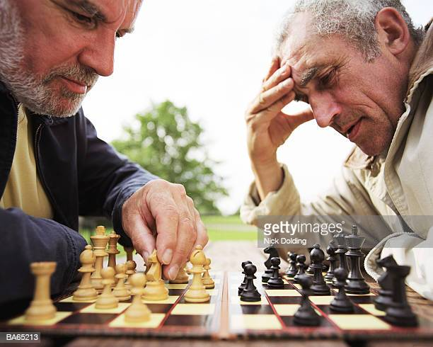 two mature men playing chess on picnic table in park, close-up - chess stock pictures, royalty-free photos & images