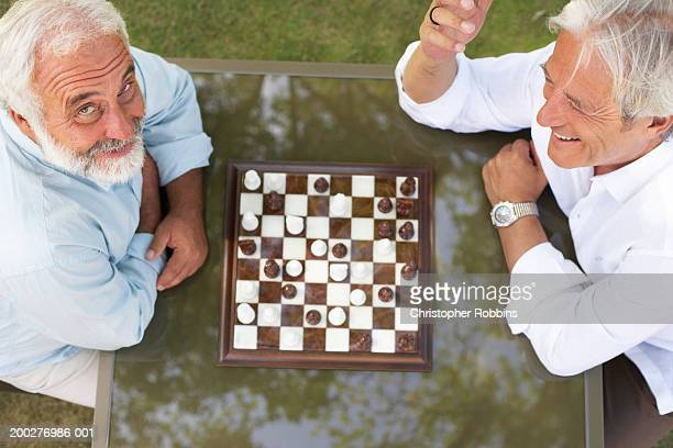 Two mature men playing chess, smiling, elevated view