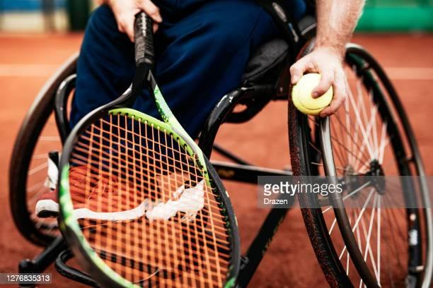 屋外で車椅子テニスでダブルスをプレーする2人の成熟した男性 - 車いすテニス ストックフォトと画像