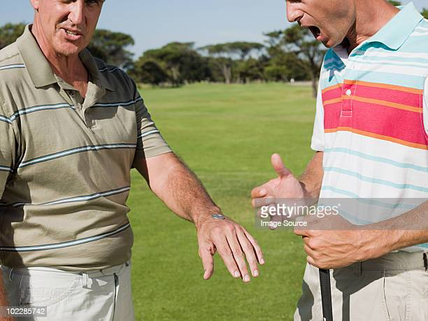 two mature men playing golf together, tossing a coin - bad luck stock pictures, royalty-free photos & images