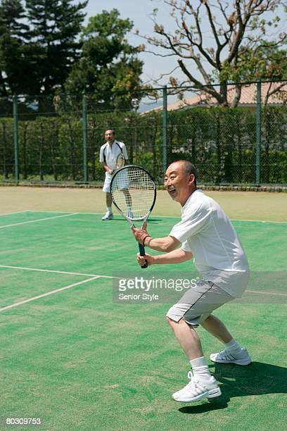 Two mature men playing tennis