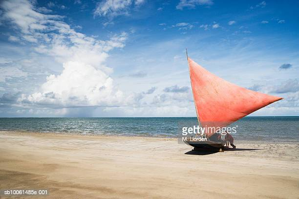 Two mature men pushing sailboat onto beach