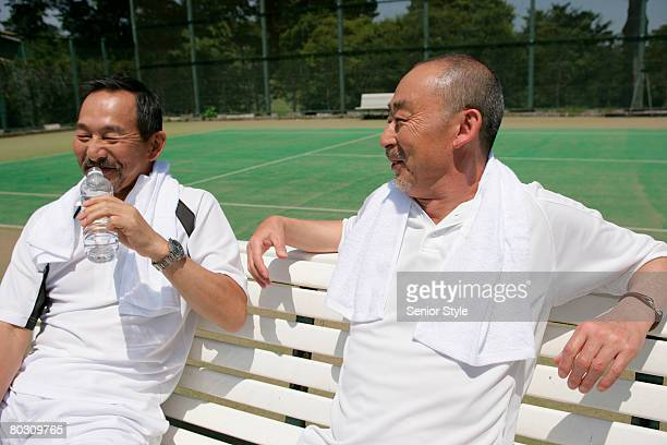 Two mature men relaxing at tennis court, close-up
